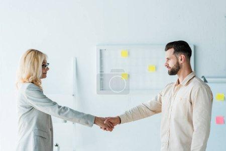 Photo pour Recruteur attrayant dans des lunettes et l'employé beau se serrant la main - image libre de droit