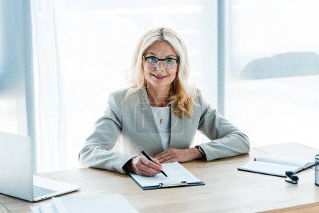 Photo for Cheerful blonde woman in glasses looking at clipboard near laptop - Royalty Free Image