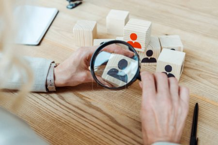 Photo for Cropped view of recruiter holding magnifier near wooden cube - Royalty Free Image