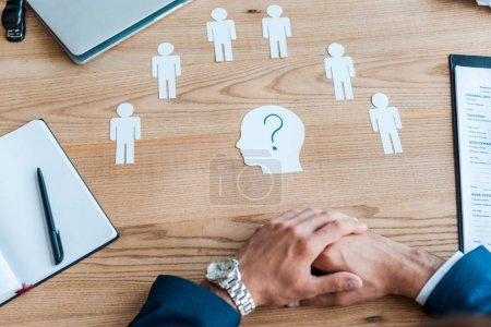 Ausgeschnittene Ansicht eines Personalvermittlers mit geballten Händen in der Nähe von Papierformen auf dem Tisch