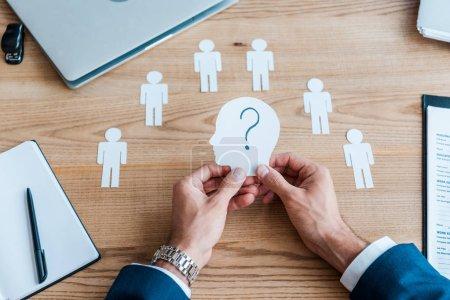 Foto de Cropped view of recruiter holding paper human shape with question mark on table - Imagen libre de derechos