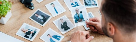 Photo for Panoramic shot of recruiter choosing while holding photo near wooden table - Royalty Free Image