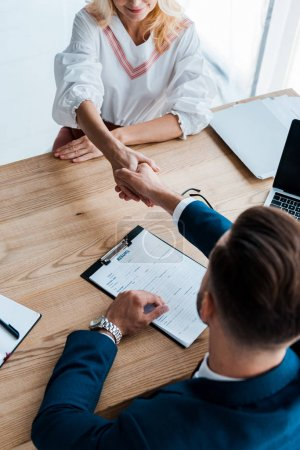 Photo pour Vue aérienne du recruteur et de l'employé heureux se serrant la main dans le bureau - image libre de droit