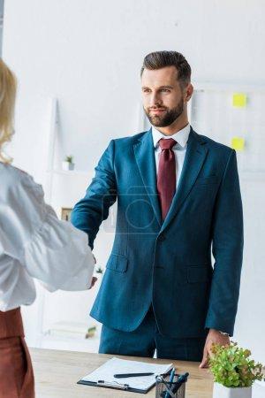 Photo pour Vue recadrée de l'employé et du recruteur beau se serrant la main - image libre de droit