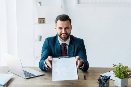 happy recruiter sitting near laptop and holding clipboard with resume