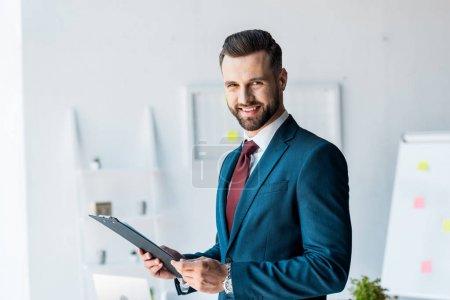Foto de Hombre barbudo alegre en traje sujetando portapapeles en la oficina - Imagen libre de derechos