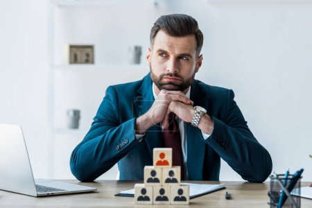 Photo for Selective focus of pensive recruiter with clenched hands near wooden cubes - Royalty Free Image