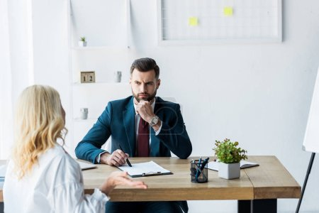 Photo for Selective focus of thoughtful recruiter in suit looking at blonde employee showing shrug gesture - Royalty Free Image