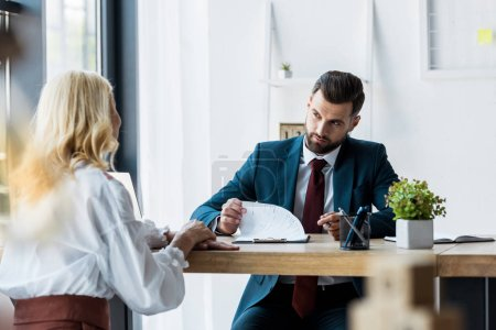 Photo for Selective focus of handsome recruiter looking at blonde employee - Royalty Free Image