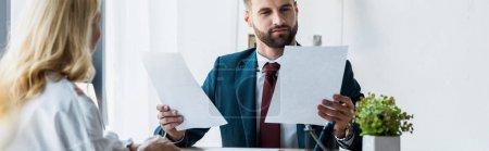 Photo pour Tir panoramique de recruteur barbu tenant des papiers près de l'employé blond - image libre de droit