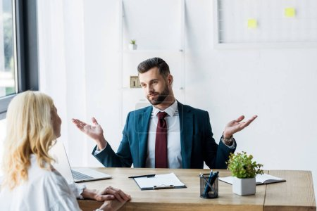 Photo for Selective focus of bearded recruiter showing shrug gesturing and looking at blonde employee - Royalty Free Image