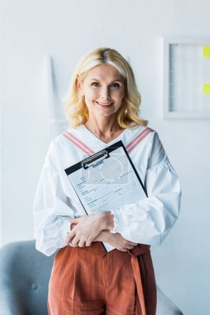 Photo for Cheerful blonde woman holding clipboard with resume in office - Royalty Free Image