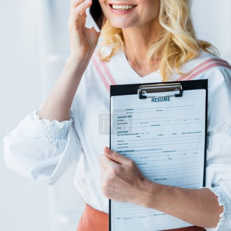 Photo pour Cropped view of happy woman talking on smartphone and holding clipboard with resume letters - image libre de droit