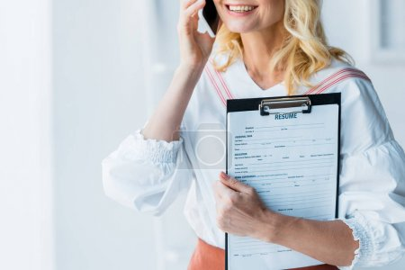cropped view of c cheerful blonde woman talking on smartphone and holding clipboard with resume letters