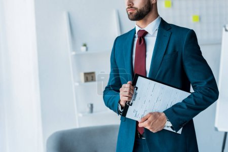 Photo for Cropped view of bearded man holding clipboard with resume letters - Royalty Free Image