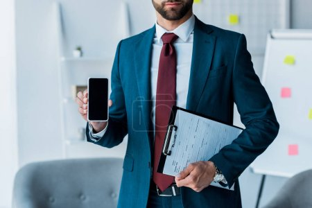 Photo for Cropped view of bearded man holding smartphone with blank screen and clipboard - Royalty Free Image