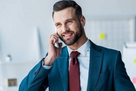 Photo pour Homme barbu gai en costume parler sur smartphone dans le bureau - image libre de droit