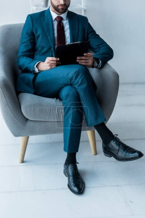 Photo for Cropped view of bearded man sitting in crossed legs and holding clipboard - Royalty Free Image