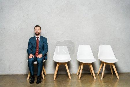 Photo pour Bel homme barbu s'asseyant sur la présidence près du mur en béton - image libre de droit