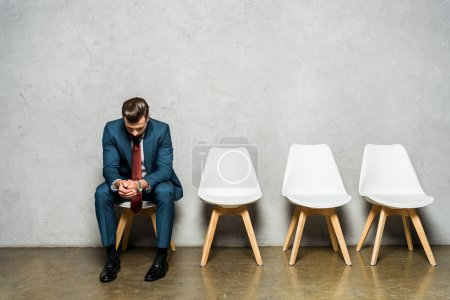 handsome man sitting with clenched hands on white chair while waiting job interviw