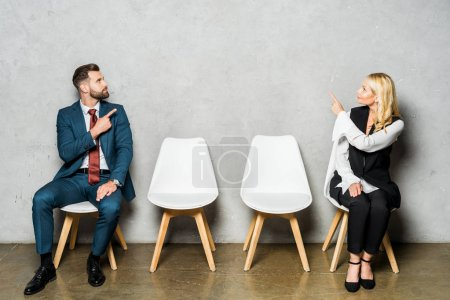 handsome bearded man and attractive blonde woman pointing with fingers while sitting on white chairs