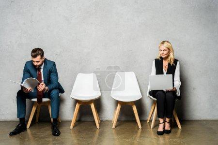 Photo pour Femme blonde attirante utilisant l'ordinateur portatif en attendant l'entrevue d'emploi près de l'homme - image libre de droit