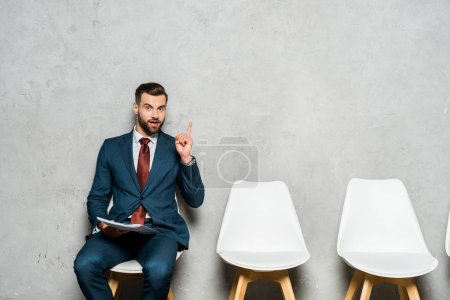 handsome bearded man gesturing while sitting on chair