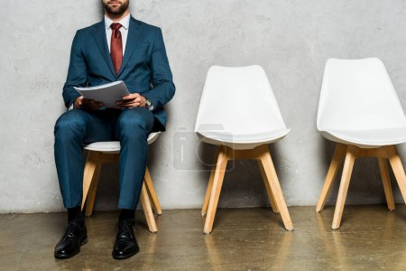 Photo for Cropped view bearded man sitting on white chair and holding folder - Royalty Free Image