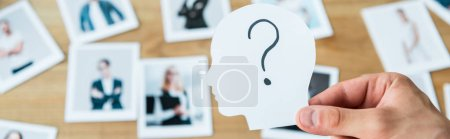 Foto de Panoramic shot of man holding paper with human head and question mark near photos - Imagen libre de derechos
