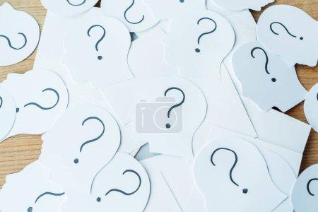 Foto de Question marks on paper with human heads on wooden table - Imagen libre de derechos