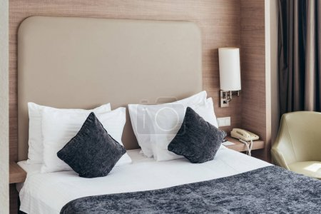 Photo for Bed with pillows and cushions in cozy hotel room - Royalty Free Image