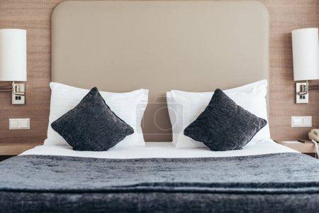 Foto de Bed with pillows and cushions in cozy hotel room - Imagen libre de derechos