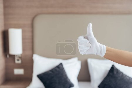 Photo for Partial view of maid in white glove showing thumb up in hotel room - Royalty Free Image