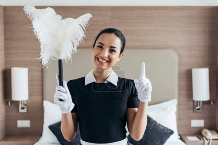 Photo for Front view of smiling maid in white gloves holding duster and showing idea sign near bed in hotel room - Royalty Free Image