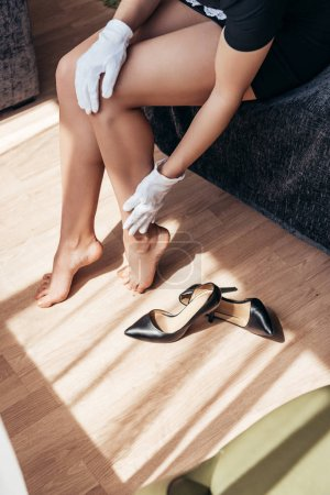 Foto de Vista parcial de la criada en guantes blancos tocando las piernas mientras se sienta en la cama - Imagen libre de derechos