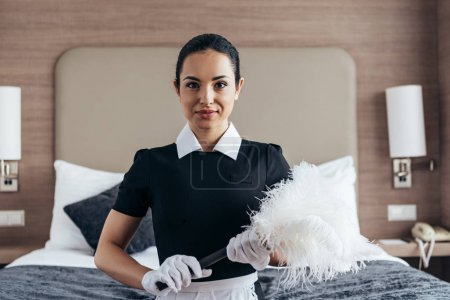 Photo for Front view of smiling maid in white gloves holding duster near bed and looking at camera - Royalty Free Image