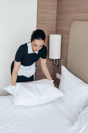 Photo pour Femme de chambre dans le tablier blanc et l'oreiller de fixation de gants dans la chambre d'hôtel - image libre de droit