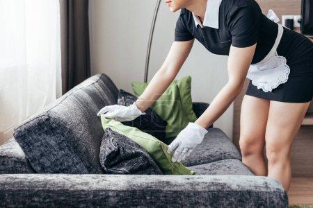 Photo pour Vue recadrée de la bonne dans le tablier blanc et le coussin de fixation de gants sur le sofa dans la chambre d'hôtel - image libre de droit