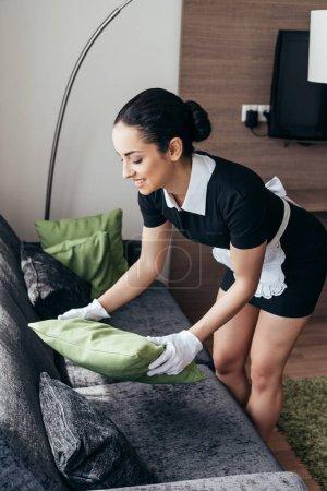 Photo pour Femme de chambre dans le tablier blanc et les gants retenant le coussin sur le sofa dans la chambre d'hôtel - image libre de droit