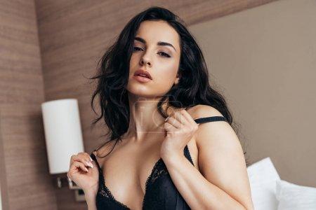 Photo pour Sexy brune jeune femme en sous-vêtements noirs sur le lit - image libre de droit