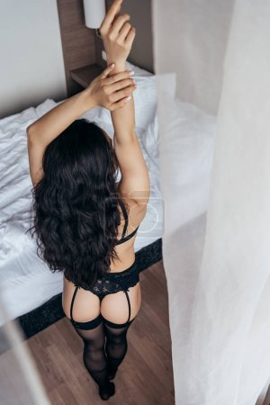 Photo for Overhead view of sexy brunette girl in black underwear standing with hands up near white curtain - Royalty Free Image