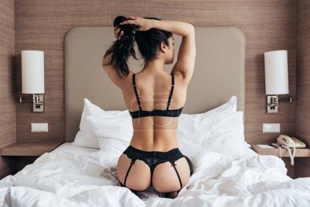 Photo pour Vue arrière de la jeune femme sexy de brunette dans la lingerie noire s'asseyant sur le lit dans la chambre d'hôtel - image libre de droit