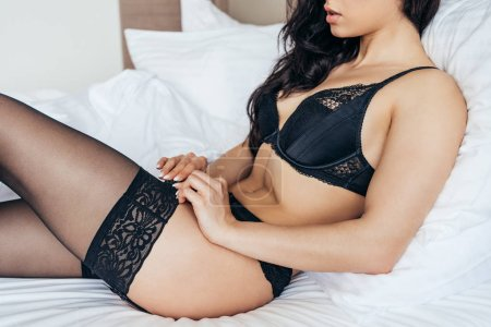 Photo for Partial view of sexy young woman in black lingerie lying on bed - Royalty Free Image