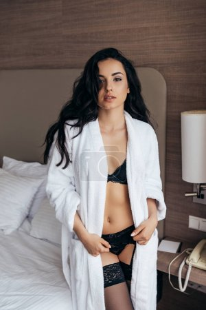 Photo pour Sexy brune jeune femme en lingerie et peignoir blanc regardant caméra dans la chambre - image libre de droit