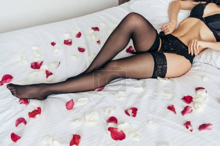 Photo for Partial view of sexy brunette girl in black lingerie on bed covered with rose petals in bedroom - Royalty Free Image