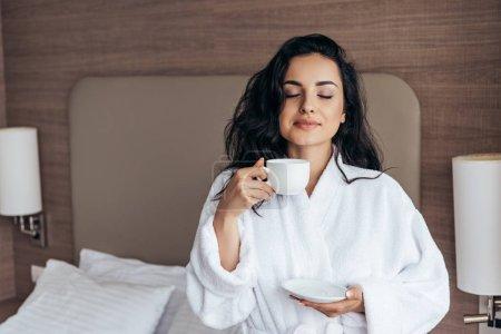 Foto de Atractiva joven en el baño blanco sosteniendo taza de café por la mañana en el dormitorio - Imagen libre de derechos