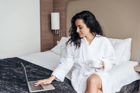Photo pour Charmante brune jeune femme dans la salle de bain blanche en utilisant un ordinateur portable et tenant une tasse de café dans la chambre - image libre de droit