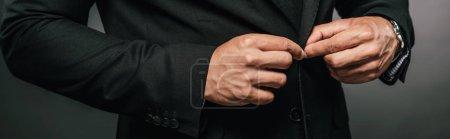 Ausgeschnittene Ansicht eines afrikanisch-amerikanischen Geschäftsmannes im Anzug Befestigungstaste auf dunklem Hintergrund, Panoramaaufnahme
