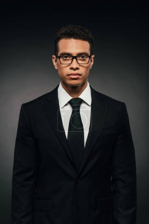 african american businessman in glasses and suit on dark background
