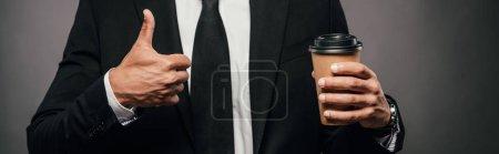 Photo pour Vue recadrée de l'homme d'affaires américain africain dans le café de fixation de procès pour aller et montrant le pouce vers le haut sur le fond foncé, projectile panoramique - image libre de droit